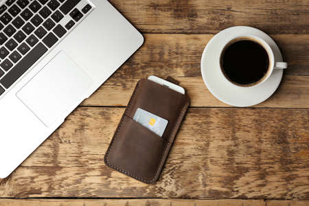 Leather case with mobile phone, laptop and cup of coffee on wooden table