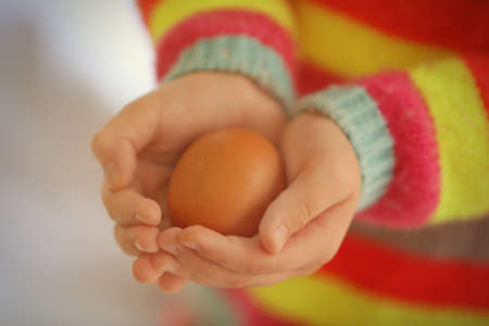 Child hands holding raw egg, closeup
