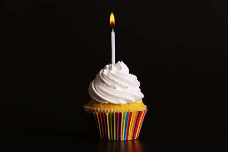 Fresh tasty cupcake with candle on dark background Imagens
