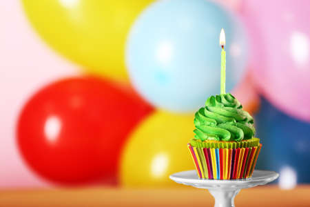 Fresh tasty cupcake with candle on colorful background