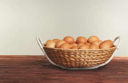 Raw eggs in wicker basket on wooden table