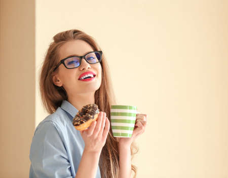 Beautiful young woman with tasty donut and cup of coffee on color background