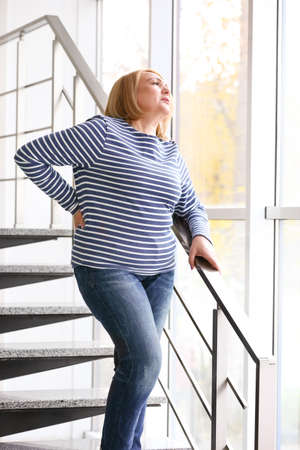 Senior woman suffering from backache while walking downstairs