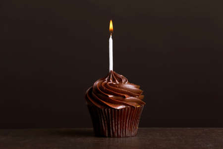Fresh tasty cupcake with candle on dark background