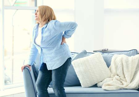 Ältere Frau, die zu Hause unter Rückenschmerzen leidet