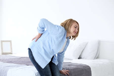 Senior woman suffering from backache at home
