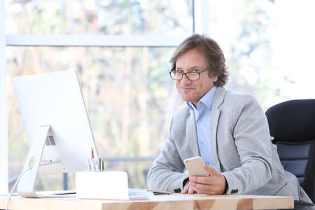 Successful mature man with mobile phone in office