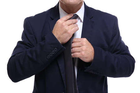 Close up view of successful businessman fixing necktie, on white background