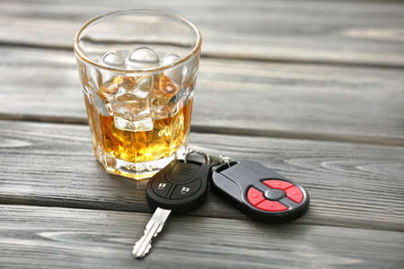 Glass with alcohol and car keys on wooden table