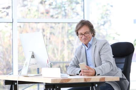 Exitoso hombre maduro con teléfono móvil en la oficina