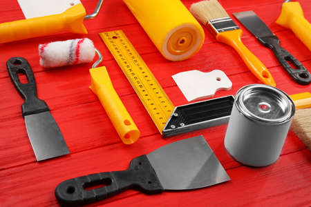 Composition of decorator and house renovation tools on wooden table Imagens