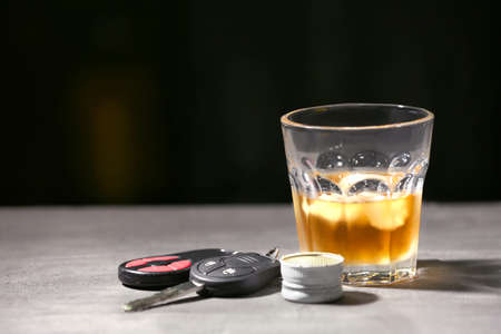 Glass with alcohol and car keys on grey table