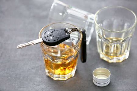 Glass with alcohol and car keys on color background