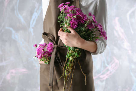 Woman florist  holding bouquet of flowers on color background