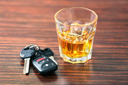 Glass with alcohol and car keys on wooden background