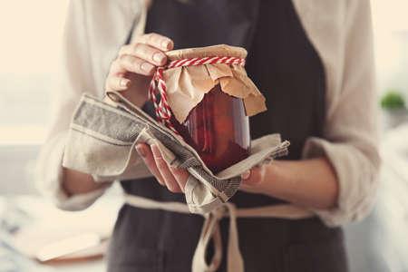 Woman in apron holding strawberry jam, closeup 版權商用圖片