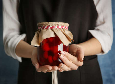 Woman in apron holding strawberry jam, closeup
