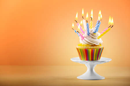 Tasty cupcake with candles on color background