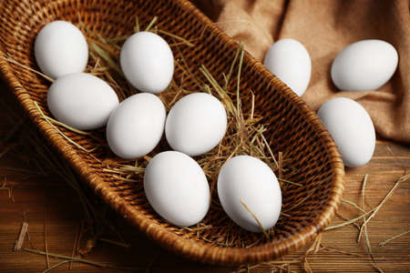 Raw eggs in basket on wooden background