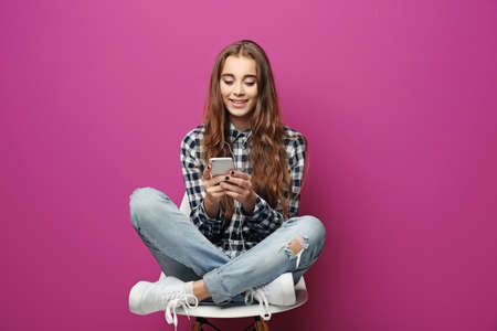 Pretty teenager girl listen music on color background