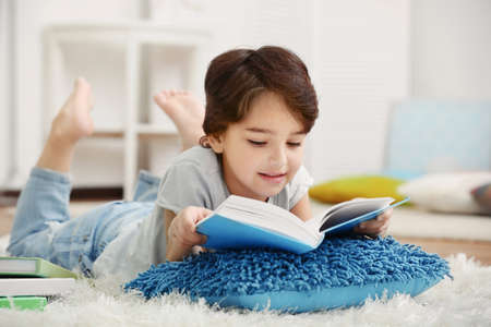 Cute little boy lying on the carpet with book on blurred background Stock Photo