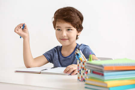 Cute little boy writing something in notebook, on white background