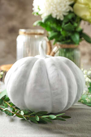 White pumpkin with eucalyptus branch on blurred background