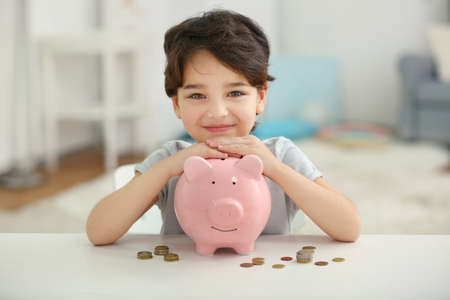 Portrait of cute little boy with piggy bank on blurred background Stock fotó