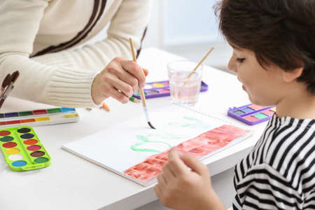 Cute little boy painting with his mother at home