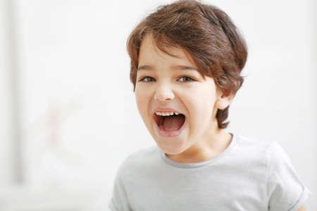 Cute emotional little boy on light blurred background
