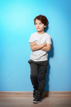 Cute emotional little boy on blue background