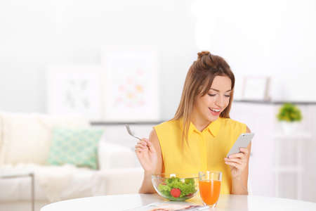 Young beautiful woman having breakfast and using smart phone
