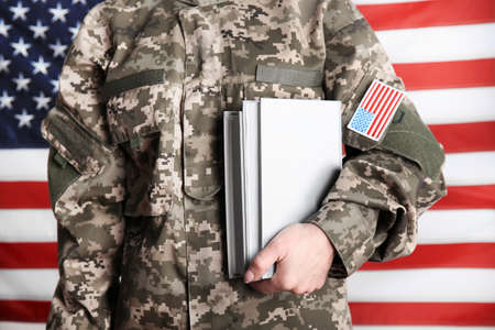 Close up view of female soldier with books on USA flag background