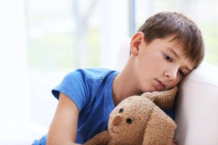 Droevige kleine jongenszitting op leunstoel, close-up
