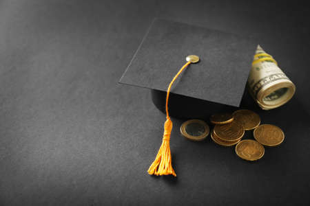 Graduation hat, dollar banknotes and coins on dark table. Pocket money concept