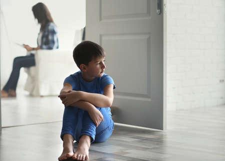 Sad little boy sitting on floor beside door