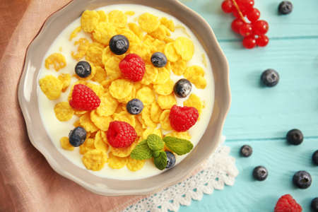 Tasty cornflakes with raspberries and blueberries on blue background