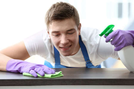 Closeup of young man cleaning table Stock Photo