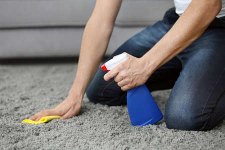 Young man cleaning carpet at home, closeup Stock Photo