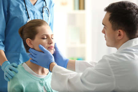 Young woman having meeting with plastic surgeon