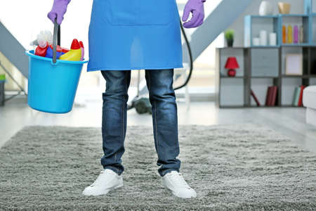 Man holding bucket with cleaning supplies indoors
