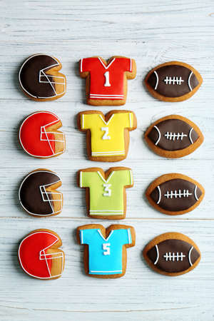 Delicious gingerbread cookies decorated with football signs on white wooden background Stock Photo