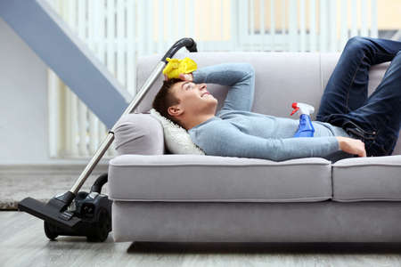 Young tired man lying on sofa after cleaning Stock Photo