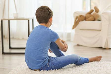 Sad little boy sitting on floor in room Stock Photo