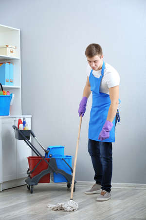 Young man with mop cleaning floor at office
