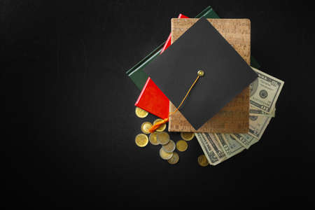 School supplies, graduation hat, banknotes and coins on dark table. Pocket money concept