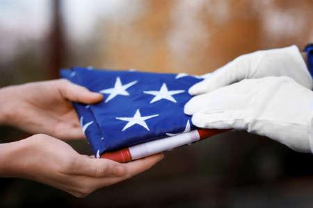 Handen die gevouwen Amerikaanse vlag op vage achtergrond houden Stockfoto