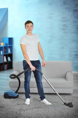 Young man with vacuum cleaner cleaning carpet at home