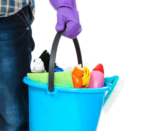 Young man holding bucket with cleaning equipment and supplies on white background, closeup Stock Photo