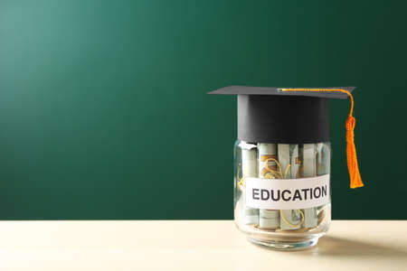 Glass jar with money for education on wooden table against green background